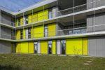 Der Neubau der Theodor-Heuglin-Schule in Ditzingen: Die Fassade ist als Pfosten-Riegel-Konstruktion mit raumhohen Verglasungen und umlaufenden Fluchtbalkonen ausgeführt. Damit der Baukörper bei heruntergefahrenem Sonnenschutz nicht zu massiv wirkt, wählte man textile ZIP-Screens, die farblich mit der Umgebung harmonieren. Quelle: GEIGER